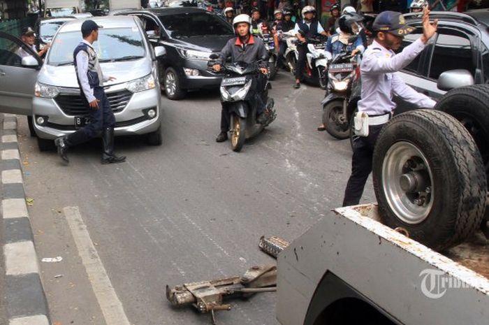 Petugas Dihub menahan mobil yang hendak kabur ketika hendak di derek karena parkir sembarangan di Jalan Kasablangka,Jakarta Selatan, Kamis(5/4/2018). Terjadi keributan kerena pemilik mobil merasa petugas Dishub pilih kasih dengan melepas mobil Ratna Sarumpaet. (Warta Kota/Henry Lopulalan)