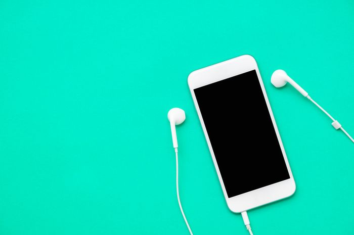 Top view of white mobile phone with headphone on fresh green background