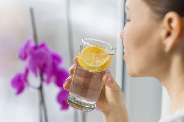 Woman drinking summer refreshing fruit flavored infused water with fresh organic lemon. Healthy eating, diet concept.