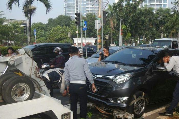 Petugas Dishub menderek mobil yang parkir sembarangan.