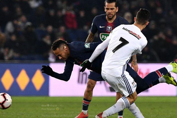 Striker Paris Saint-Germain, Neymar, terjatuh menghindari hadangan pemain Strasbourg, Moataz Zemzemi