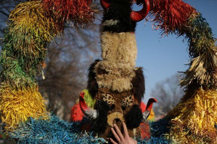 Seorang penari menahan topengnya saat mengikuti Karnaval Topeng Internasional 'Surva'.