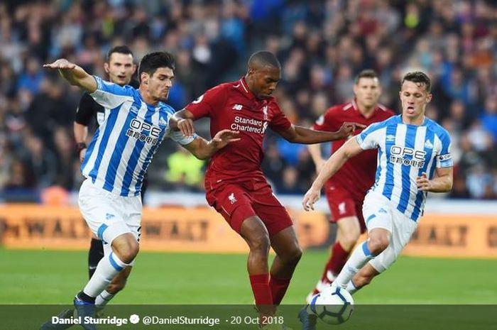 Striker Liverpool, Daniel Sturridge, berjibaku mempertahankan bola saat dikepung pemain Huddersfield Town dalam laga lanjutan Liga Inggris pada Sabtu (20/10/2018) di Stadion John Smith.