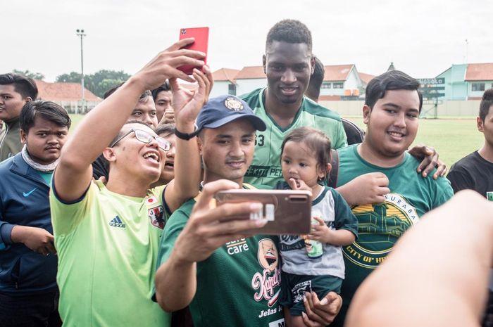 Penyerang anyar Persebaya Surabaya, Amido Balde, melayani sesi foto suporter.