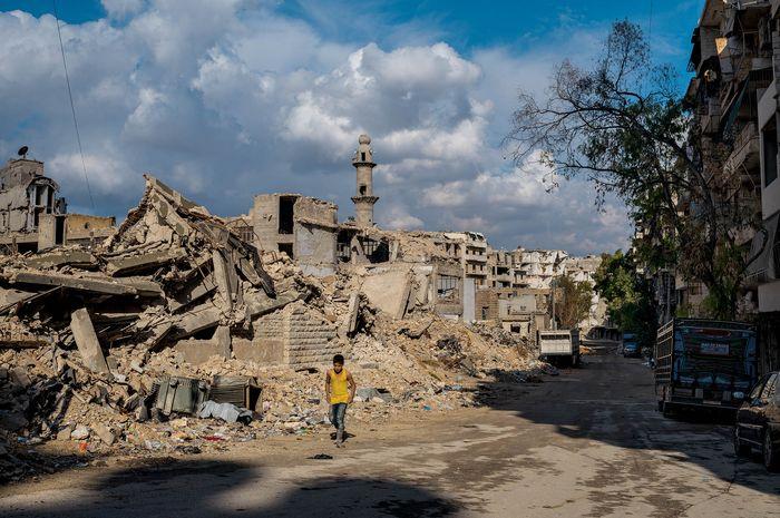 Seorang anak laki-laki berjalan di depan bekas sekolah dan masjid di lingkungan Sukkari di Aleppo selatan. Masjidnya dibangun kembali sementara sebagian besar bangunan di sekitar situ masih berupa reruntuhan.