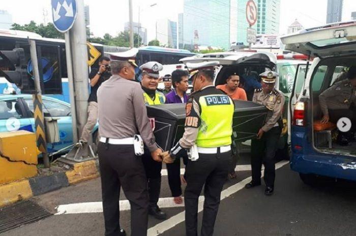 Polisi ikut membantu warg memindahkan peti ke ambulans