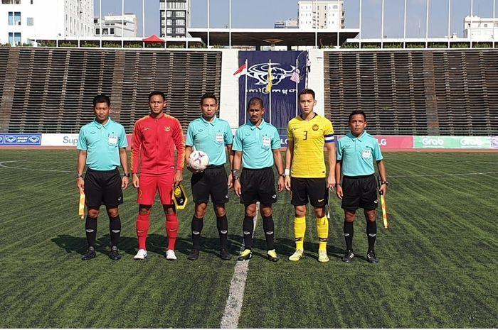 Kapten timnas U-22 Indonesia, Andy Setyo Nugroho, bersama perangkat pertandjngan dan kapten Malaysia, Dominic Tan sebelum laga Piala AFF U-22 2019 di Stadion Nasional, Phnom Penh, Rabu (20/2/2019).