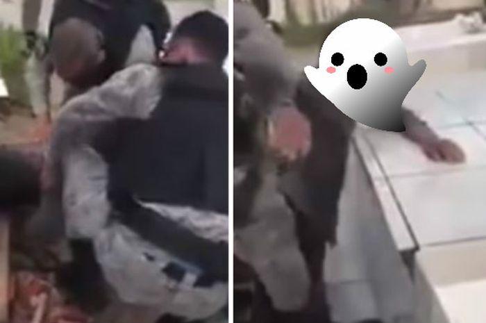 Petugas polisi mengeluarkan seorang pria dari dalam sebuah makam.