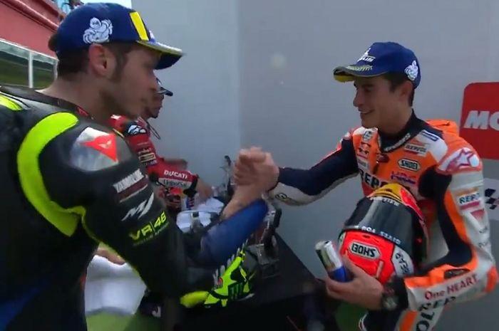 Momen saat Valentino Rossi (kiri) dan Marc Marquez (kanan) berjabat tangan sesaat sebelum prosesi penyerahan trofi MotoGP Argentina 2019 dilakukan.