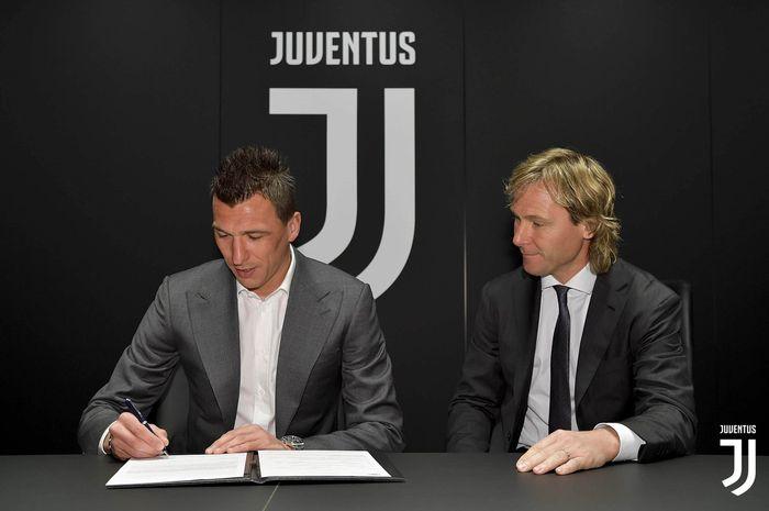 Mario Mandzukic menandatangani kontrak baru bersama Wakil Presiden Juventus, Pavel Nedved, pada Kamis (4/4/2019).