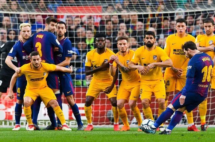 Striker Barcelona Lionel Messi mengeksekusi tendangan bebas ke gawang Atletico Madrid.