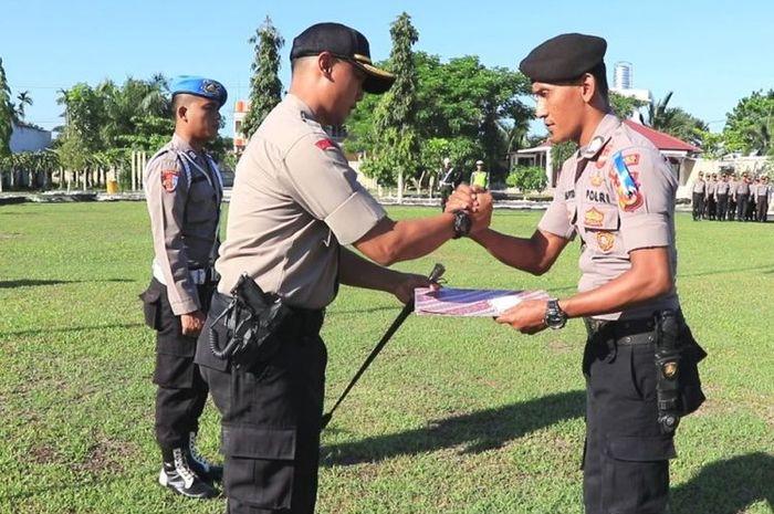 Brigadir Teuku Putra mendapat penghargaan dari Kapolres Aceh Utara atas tugasnya menjaga PPK sambil menidurkan anaknya.