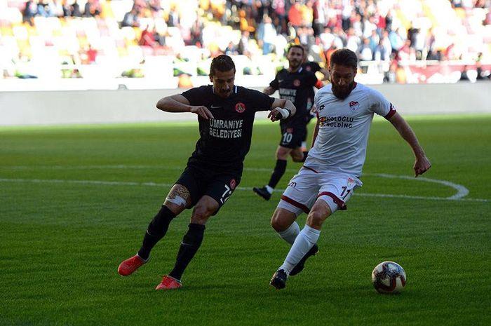 Pemain Elazigspor, Serdar Ozbayraktar (kanan) berebut bola dengan pilar Umraniyespor, Mohammed Gonulacar pada lanjutan kasta kedua Liga Turki, 4 Mei 2019.