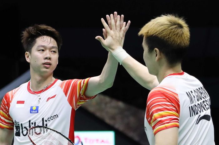Pasangan ganda putra Indonesia, Marcus Fernaldi Gideon/Kevin Sanjaya Sukamuljo, melakukan tos seusai memenangi pertandingan melawan Marcus Ellis/Chris Langridge pada penyisihan Grup B Piala Sudirman 2019 kontra Inggris di Guangxi Sports Center Gymnasium, Nanning, China, Minggu (19/5/2019).