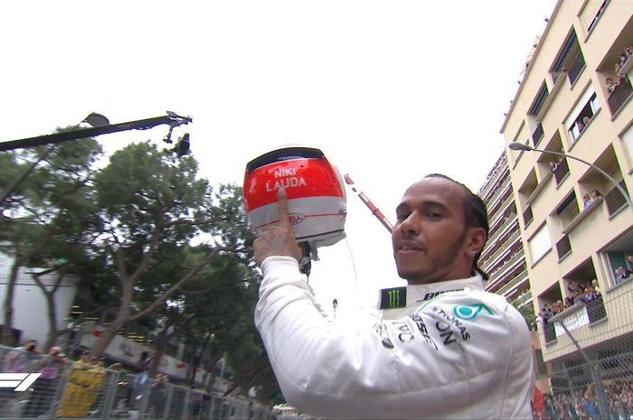 Momen saat Lewis Hamilton (Mercedes) mengangkat helm bertulis Niki Lauda sesaat setelah sukses memenagi F1 GP Monako 2019, Minggu (26/5/2019).