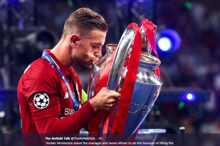 Kapten Liverpool, Jordan Henderson, mencium trofi Liga Champions usai Liverpool mengalahkan Tottenham Hotspur pada final Liga Champions di Stadion Metropolitano, Sabtu (1/6/2019)