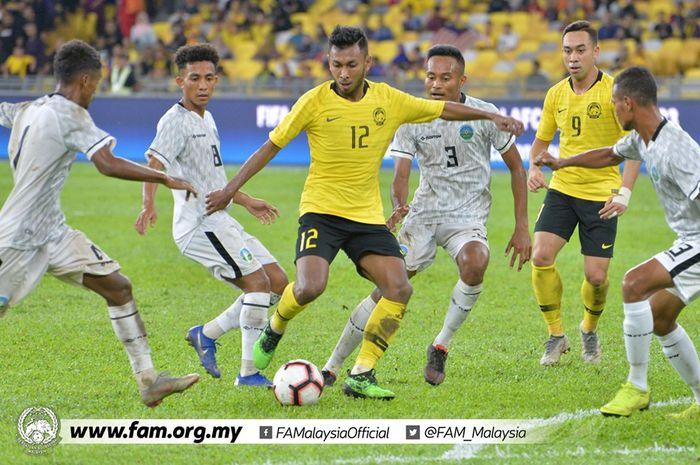 Gelandang timnas Malaysia, Akram Mahinan (12) di antara empat pemain timnas Timor Leste pada laga leg pertama fase awal Kualifikasi Piala Dunia 2022/Piala Asia 2023 di Stadion Nasional Bukit Jalil, Kuala Lumpur pada 7 Juni 2019.