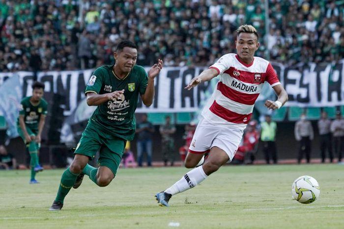 Pemain Madura United, Asep Berlian (kanan), berebut bola dengan Oktafianus Fernando, gelandang Persebaya (kiri) pada leg pertama babak 8 besar Piala Indonesia 2018 di Stadion Gelora Bung Tomo, Surabaya, Rabu (19/6/2019).