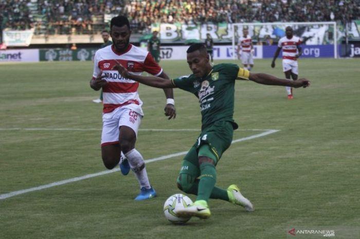 Kapten Persebaya Surabaya, Ruben Sanadi, saat berebut bola dengan bek Madura United, Marckho Sandy Meraudje, pada leg pertama perempat final Piala Indonesia 2018.