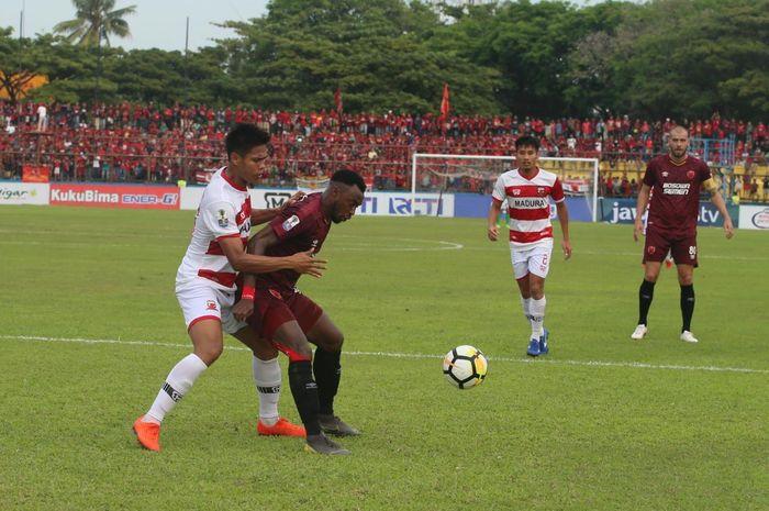 Bek Madura United menjaga ketat penyerang PSM Makassar, Guy Junior pada semifinal pertama Piala Indonesia 2018 di Stadion Andi Mattalatta, Kota Makassar, 30 Juni 2019.