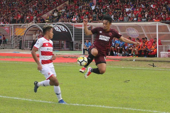 Bek sayap PSM Makassar, Beny Wahyudi melakukan kontrol bola di udara dan diawasi gelandang Madura United, Asep Berlian pada semifinal pertama Piala Indonesia 2018 di Stadion Andi Mattalatta, Kota Makassar, 30 Juni 2019.
