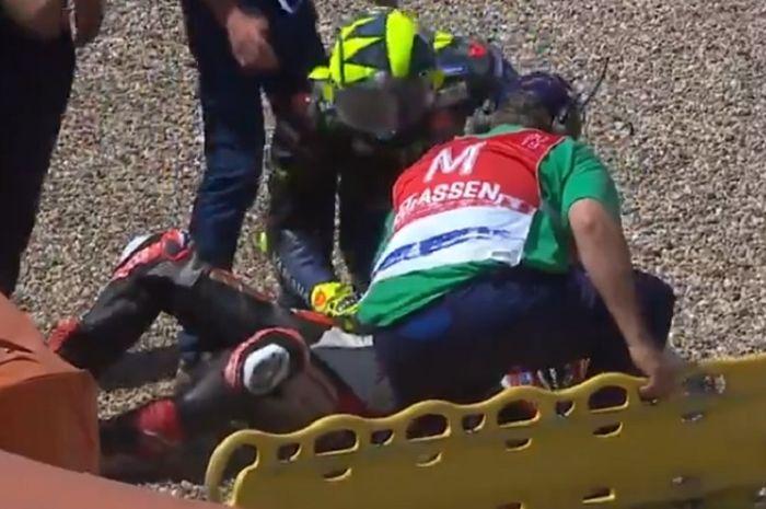 Momen saat Valentino Rossi mengecek kondisi Takaaki Nakagami setelah terlibat insiden kecelakaan pada MotoGP Belanda 2019, Minggu (30/6/2019)