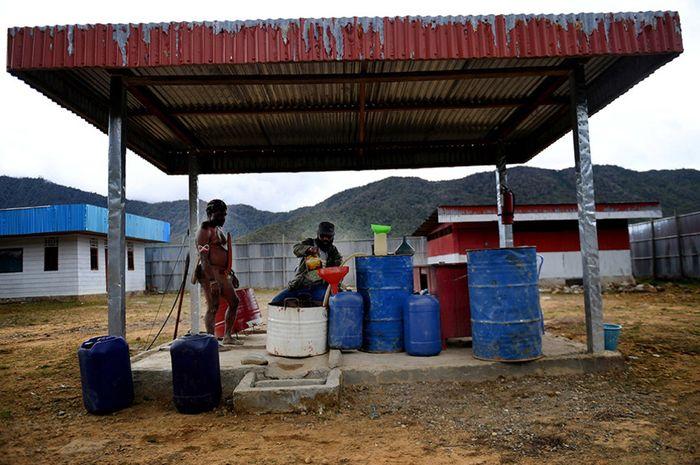 Petugas melayani warga yang membeli BBM di SPBU Kompak, Kampung Obano, Distrik Paniai Barat, Papua, Kamis (29/11/2018). Meski dengan upaya distribusi yang tidak mudah, program BBM satu harga menjadi sangat vital bagi masyarakat pedalaman Papua guna mendukung berbagai aktivitas mereka.
