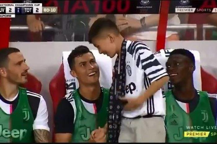 Seorang penyusup cilik disambut Cristano Ronaldo, Leonardo Bonucci, dan Idrissa Toure, saat laga International Champions Cup 2019.