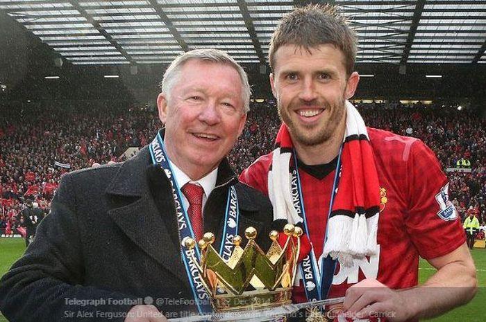 Legenda Manchester United, Michael Carrick mengangangkat trofi juara Liga Inggris musim 2012-2013 bersama pelatih The Red Devils saat itu, Sir Alex Ferguson.
