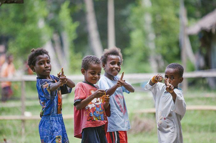Anak-anak menghabiskan waktu siang hari dengan bermain karet bersama di salah satu halaman rumah di desa Yeflio, distrik Mayamuk, Sorong, Papua Barat.