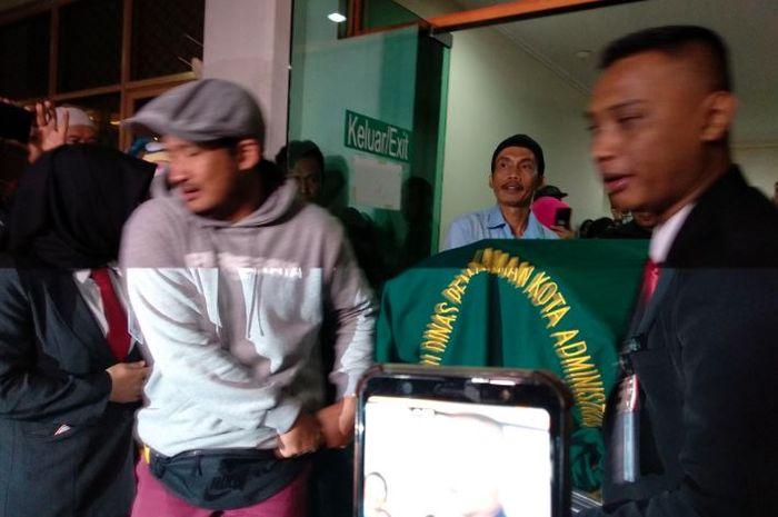 komedian Isa Bajaj beserta keluarga Agung Hercules membawa keranda jenazah Agung Hercules ke dalam ambulance di rumah sakit Dharmais, Jakarta Barat, Kamis (1/8/2019).