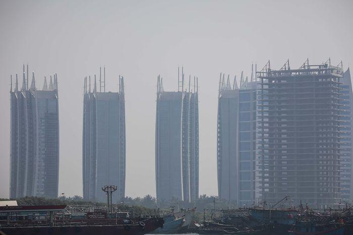 Pemandangan laut dengan latar belakang gedung bertingkat yang diselimuti asap polusi di Jakarta Utara, Rabu (31/7/2019). Berdasarkan data situs penyedia peta polusi daring harian kota-kota besar di dunia AirVisual, menempatkan Jakarta pada urutan pertama kota terpolusi sedunia pada Senin (29/7) pagi