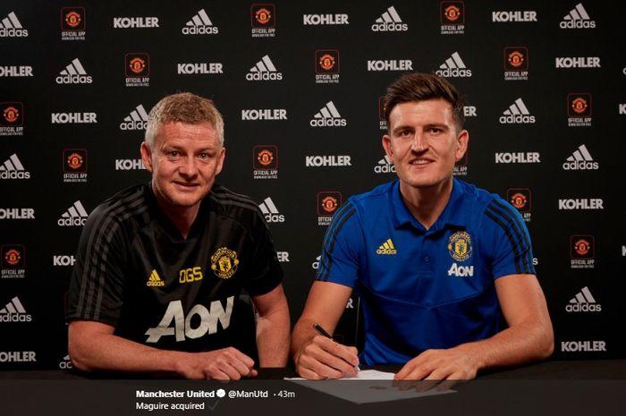 Harry Maguire (kanan) menandatangani kontrak dengan Manchester United didampingi pelatih klub, Ole Gunnar Solskjaer.