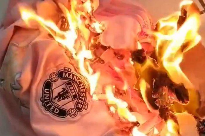 Suporter Manchester United membakar jersey klub.