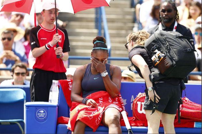 Serena Williams (duduk) saat memutuskan untuk mengundurkan diri pada laga final Rogers Cup 2019, Minggu (11/8/2019) waktu setempat