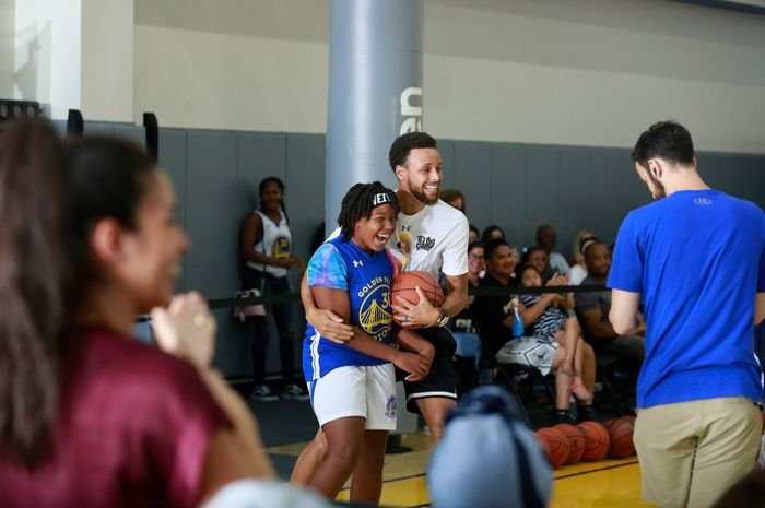Pemain Golden State Warriors, Stephen Curry, memeluk salah satu peserta Warriors Summer Camp.