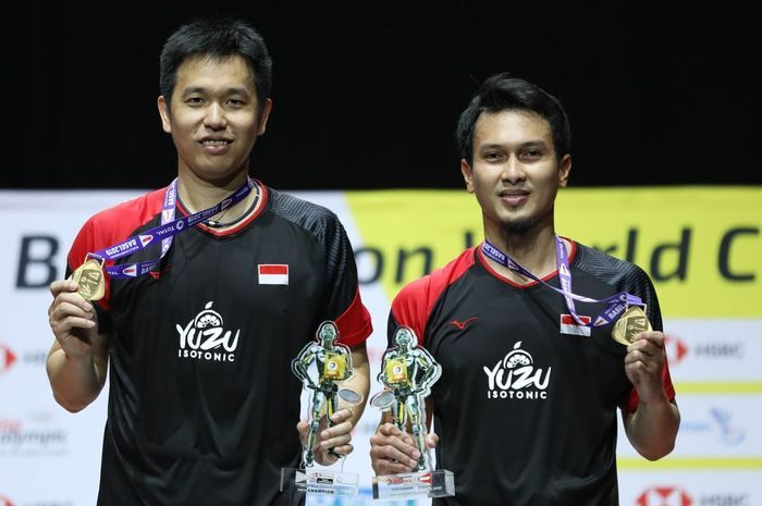 Pasangan ganda putra Indonesia, Hendra Setiawan dan Mohammad Ahsan, berpose dengan medali emas Kejuaraan Dunia 2019 yang mereka raih pada babak final di Basel, Swiss, Minggu (26/8/2019).