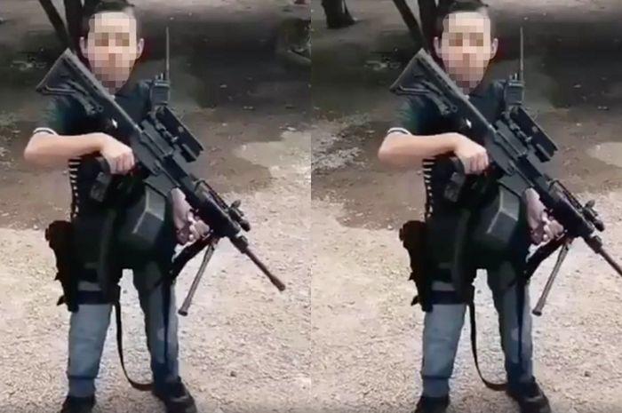 Seorang anak-anak membawa senjata laras panjang.