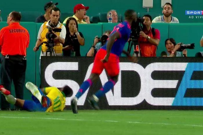 Penyerang timnas Brasil, Neymar (bawah), jatuh menabrak papan iklan setelah didorong bek Kolombia, Davinson Sanchez.