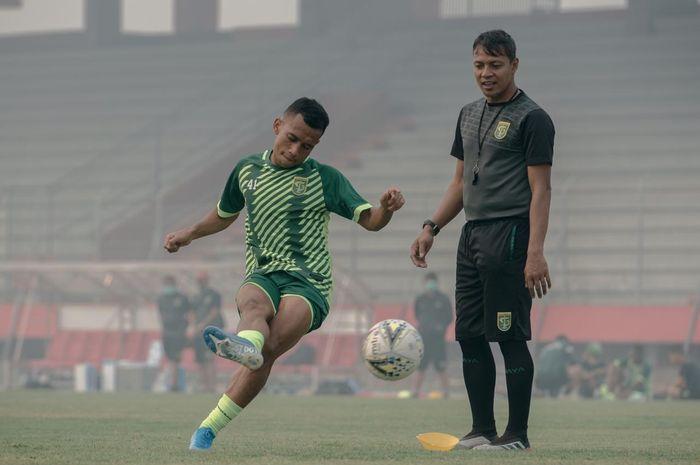 Asisten pelatih Persebaya Bejo Sugiantoro (kanan) melihat langsung aksi Irfan Jaya menendang bola pada sesi match official training di Stadion Tuah Pahoe, Palangkaraya.