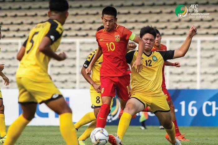 Kapten timnas U-16 China, He Xiaoke (10) coba dihentikan pilar bertahan timnas U-16 Brunei, Danial Hariz pada laga pertama Grup G Kualifikasi Piala Asia U-16 2020 di Stadion Madya Gelora Bung Karno, Senayan, Jakarta Pusat, 14 September 2019.