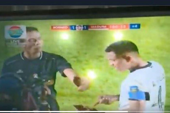 Kapten Madura United, Asep Berlian, meminta wasit Nusur Fadilah melihat tayangan ulang dari ponsel.