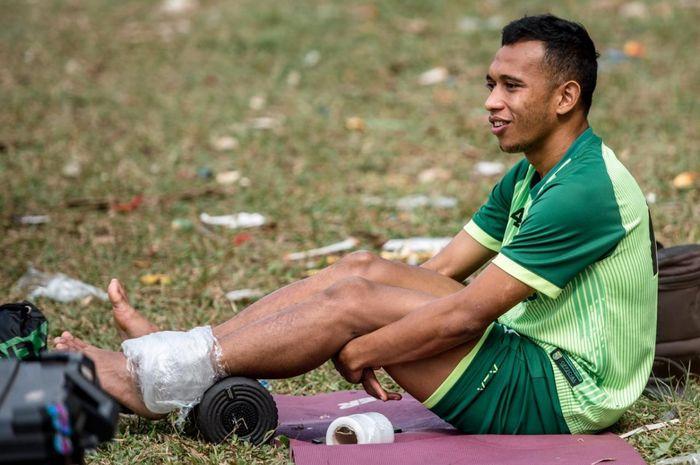 Winger Persebaya Surabaya, Irfan Jaya, mendapatkan perawatan sembari menyaksikan rekan-rekannya menjalani recovery training di Lapangan Bromo Kalinegoro Mertoyudan, Magelang, Minggu (21/9/2019).