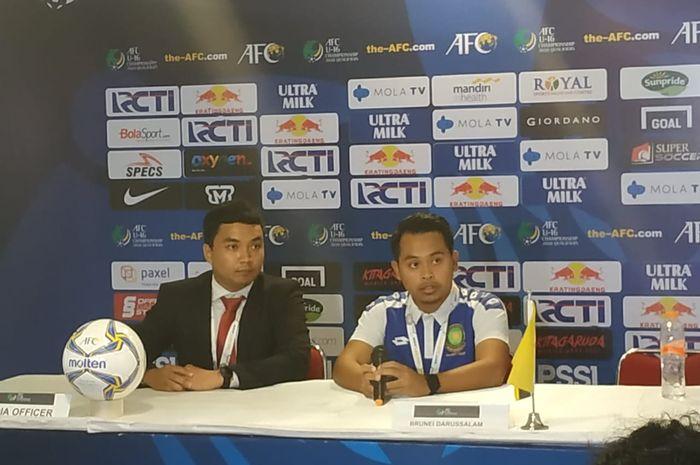 Pelatih timnas U-16 Brunei, Mohammad Ikhmarol Izzat (kanan) saat memberikan keterangan pers seusai laga kontra timnas U-16 Indonesia, Jumat (20/9/2019).