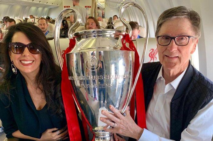 Pemilik Liverpool dan Boston Red Sox, John W Henry, berpose dengan trofi Liga Champions 2019 yang dimenangkan The Reds seusai mengalahkan Tottenham.