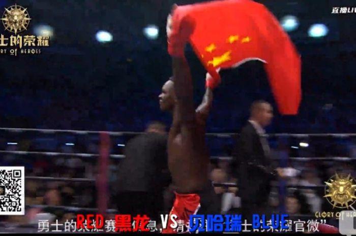 Israel Adesanya merayakan kemenangan di ring dengan bendera China.