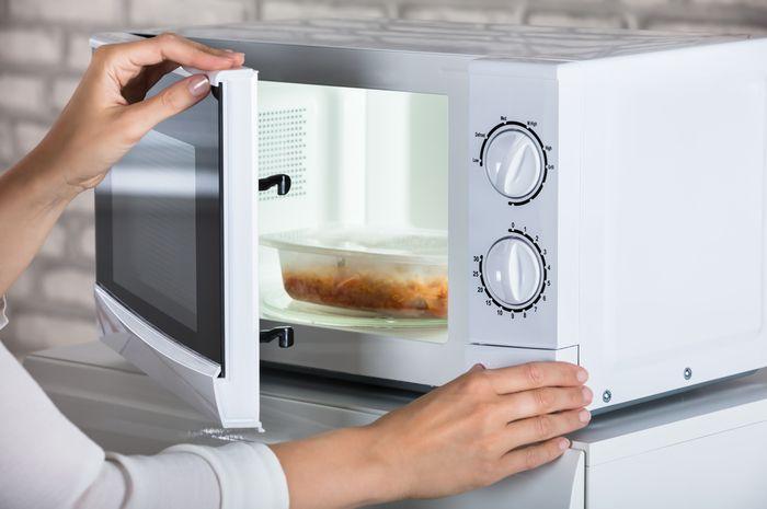 Ilustrasi memanaskan makanan di dalam microwave.