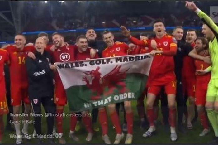 Pemain sayap timnas Wales, Gareth Bale, membawa bendera sindiran untuk klubnya, Real Madrid, saat merayakan kelolosan ke Piala Eropa 2020.
