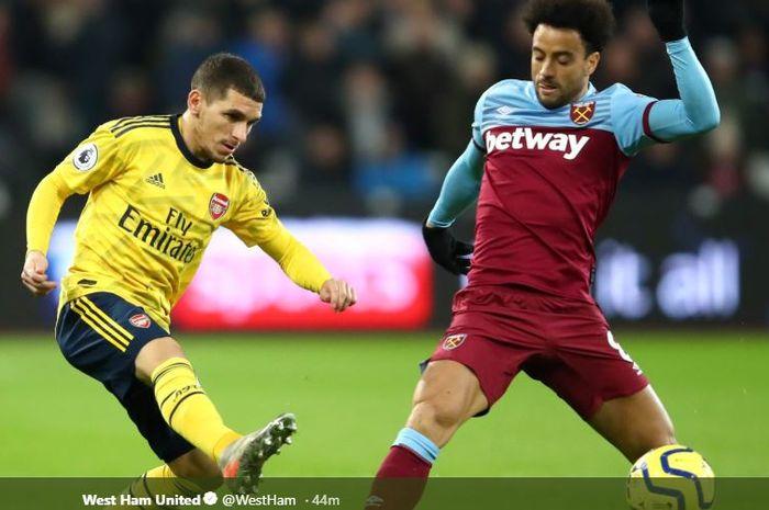 Gelandang Arsenal, Lucas Torreira, dihadang winger West Ham Felipe Anderson pada laga Liga Inggris, Selasa (10/12/2019) di Stadion London.