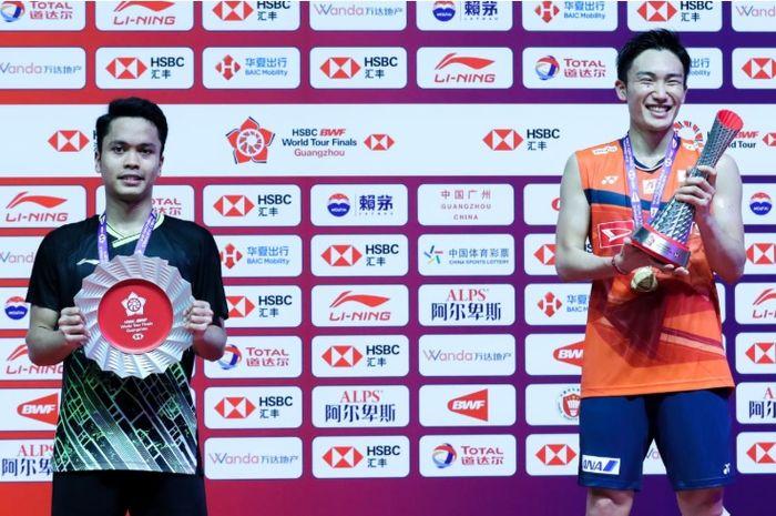 Anthony Sinisuka Ginting (kiri) dan Kento Momota (kanan) keduanya menerima piala setelah berjuang di final BWF World Tour Finals 2019 di Tianhe Gymnasium, Guangzhou, China, Minggu (15/12/2019).